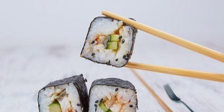 chopsticks holding sushi